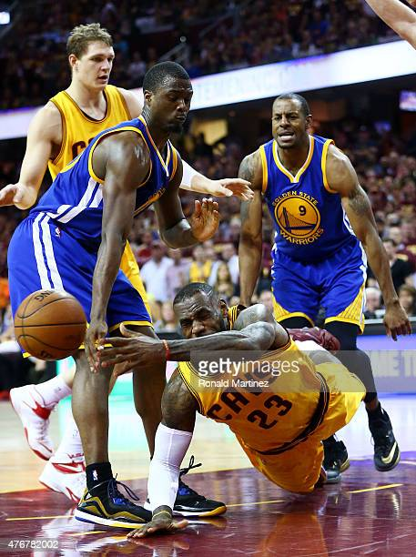 LeBron James of the Cleveland Cavaliers falls to the court as Harrison Barnes of the Golden State Warriors defends in the third quarter during Game...