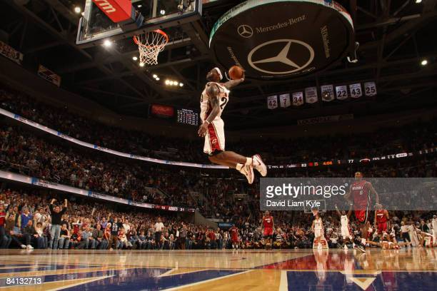 LeBron James of the Cleveland Cavaliers flies in for the dunk trailed by Mario Chalmers of the Miami Heat at The Quicken Loans Arena on December 28...