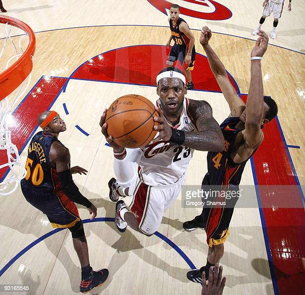 LeBron James of the Cleveland Cavaliers gets to the basket between Corey Maggette and Anthony Randolph of the Golden State Warriors on November 17...