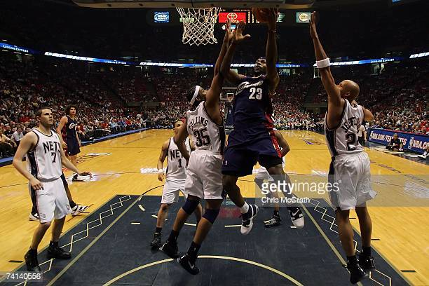 LeBron James of the Cleveland Cavaliers goes to the hoop Jason Collins and Richard Jefferson of the New Jersey Nets during Game Three of the Eastern...
