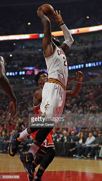LeBron James of the Cleveland Cavaliers goes up for a dunk over Jimmy Butler of the Chicago Bulls at the United Center on April 9 2016 in Chicago...