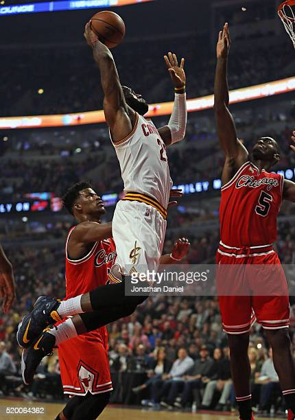LeBron James of the Cleveland Cavaliers goes up for a dunk over Jimmy Butler and Bobby Portis of the Chicago Bulls at the United Center on April 9...