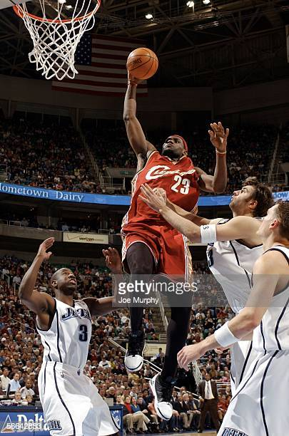 Lebron James of the Cleveland Cavaliers goes up for a dunk over Mehmet Okur and Milt Palacio of the Utah Jazz during a game between the Cleveland...