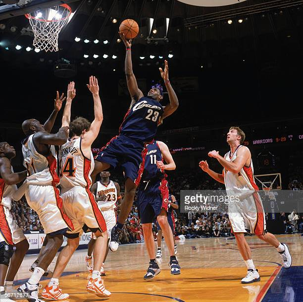LeBron James of the Cleveland Cavaliers goes up for a shot against Adonal Foyle and Mike Dunleavy of the Golden State Warriors during a game at The...
