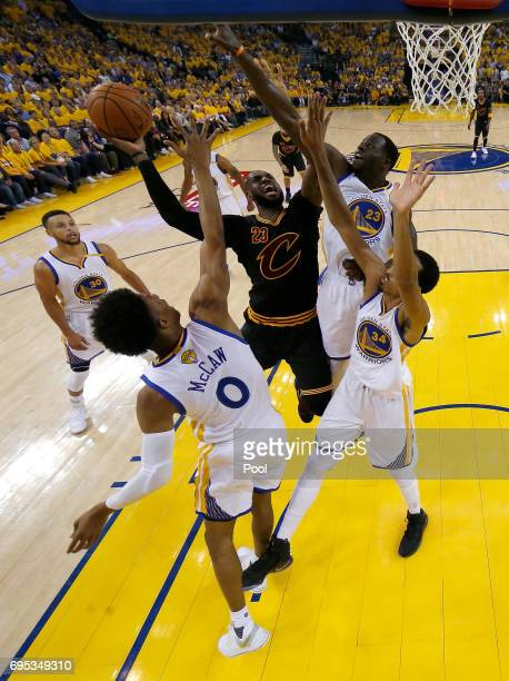 LeBron James of the Cleveland Cavaliers goes up for a shot against Patrick McCaw Shaun Livingston and Draymond Green of the Golden State Warriors in...
