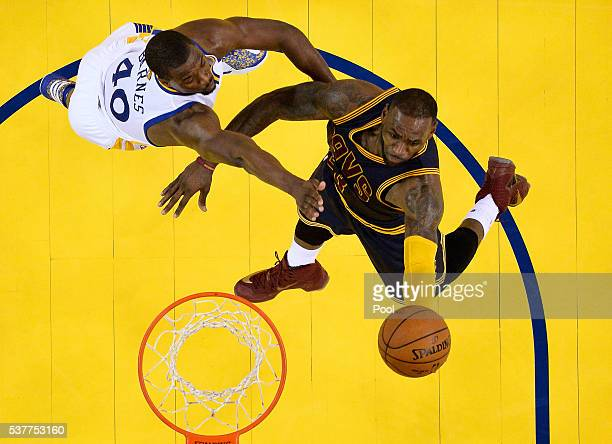 LeBron James of the Cleveland Cavaliers goes up for a shot in the lane against Harrison Barnes of the Golden State Warriors in the second half in...