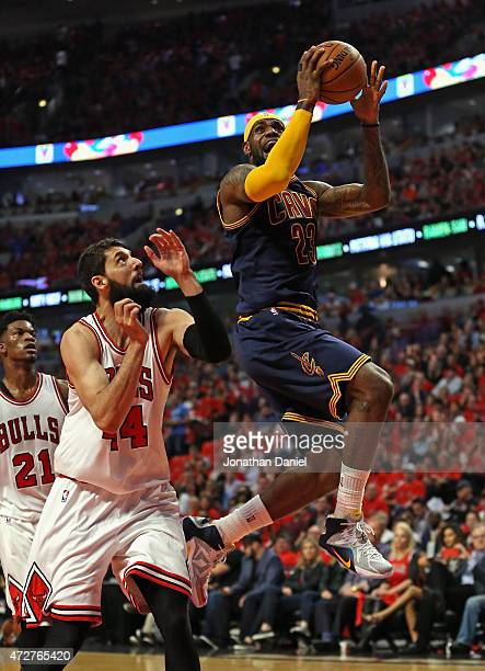 LeBron James of the Cleveland Cavaliers goes up for a shot past Nikola Mirotic of the Chicago Bulls in Game Three of the Eastern Conference...
