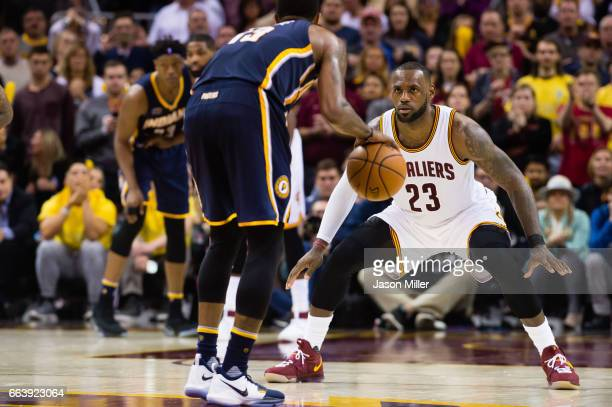 LeBron James of the Cleveland Cavaliers guards Paul George of the Indiana Pacers during the second half at Quicken Loans Arena on April 2 2017 in...