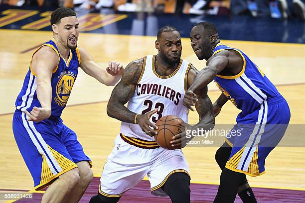 LeBron James of the Cleveland Cavaliers handles the ball against Klay Thompson of the Golden State Warriors and Draymond Green during the first half...