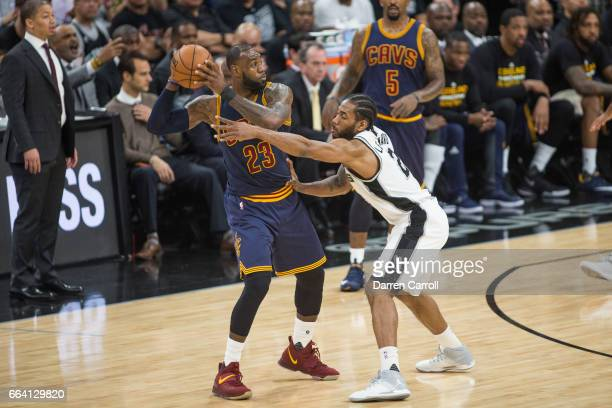 LeBron James of the Cleveland Cavaliers handles the ball against Kawhi Leonard of the San Antonio Spurs on March 27 2017 at the ATT Center in San...