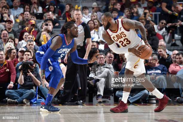 LeBron James of the Cleveland Cavaliers handles the ball against Montrezl Harrell of the LA Clippers on November 17 2017 at Quicken Loans Arena in...