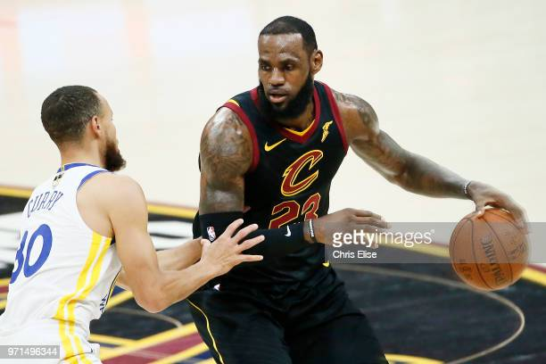 LeBron James of the Cleveland Cavaliers handles the ball against Stephen Curry of the Golden State Warriors in Game Four of the 2018 NBA Finals won...