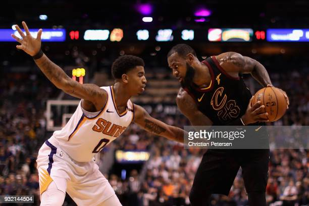 LeBron James of the Cleveland Cavaliers handles the ball under pressure from Marquese Chriss of the Phoenix Suns during the first half of the NBA...