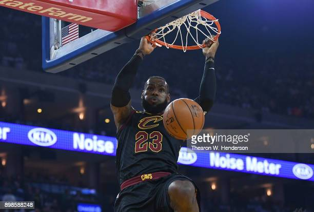 LeBron James of the Cleveland Cavaliers hangs onto the rim after a slam dunk against the Golden State Warriors during an NBA basketball game at...