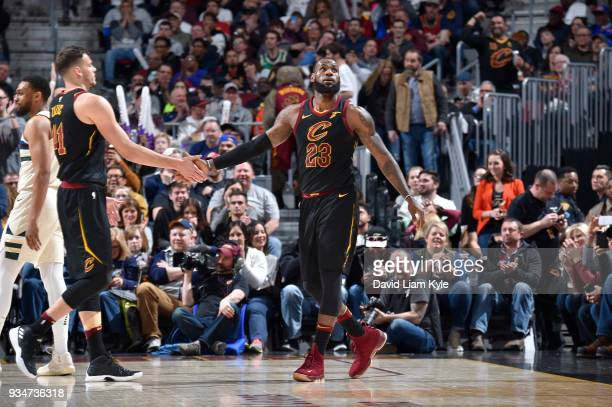 LeBron James of the Cleveland Cavaliers high fives Ante Zizic of the Cleveland Cavaliers during the game against the Milwaukee Bucks on March 19 2018...