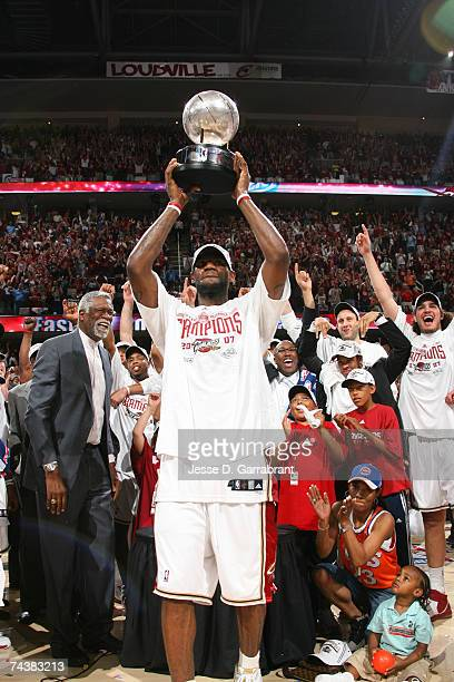 LeBron James of the Cleveland Cavaliers hoists the Eastern Conference Championship trophy over his head following Game Six of the Eastern Conference...