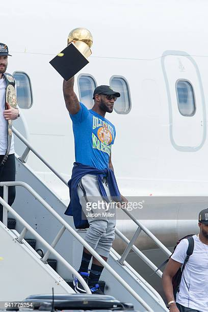 LeBron James of the Cleveland Cavaliers hoists the trophy as he gets off the plane as the team returns to Cleveland after wining the NBA...