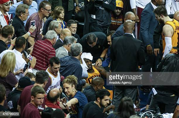 LeBron James of the Cleveland Cavaliers holds his head after falling into the media in the second quarter against the Golden State Warriors during...