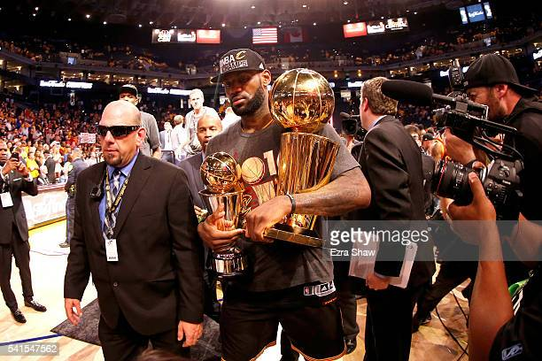 LeBron James of the Cleveland Cavaliers holds the Larry O'Brien Championship Trophy and the Bill Russell NBA Finals Most Valuable Player Award after...