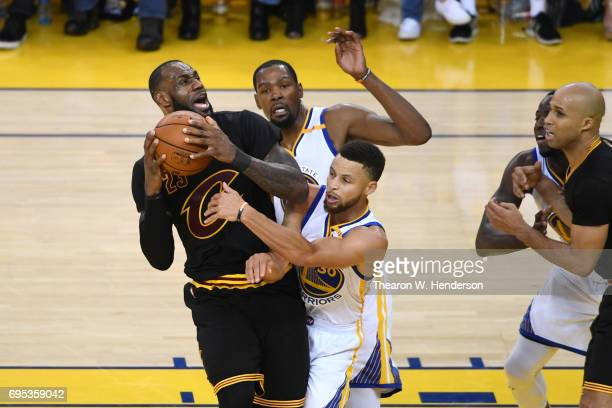 LeBron James of the Cleveland Cavaliers is defended by Kevin Durant and Stephen Curry of the Golden State Warriors during the second half in Game 5...