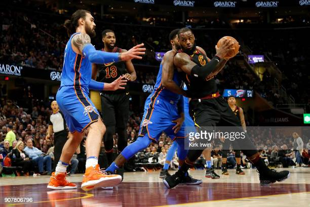 LeBron James of the Cleveland Cavaliers is defended in the key by Paul George of the Oklahoma City Thunder and Steven Adams of the Oklahoma City...
