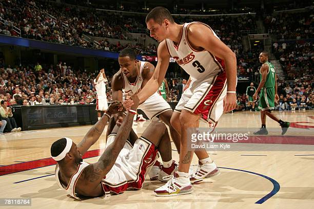 LeBron James of the Cleveland Cavaliers is helped up by teammates Damon Jones and Sasha Pavlovic during a game against the Boston Celtics November...