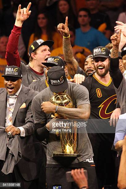 LeBron James of the Cleveland Cavaliers kisses the Larry O'Brien Trophy after the 2016 NBA Finals Game Seven against the Golden State Warriors on...