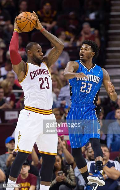 LeBron James of the Cleveland Cavaliers looks for a pass over CJ Wilcox of the Orlando Magic during the first half of a preseason game at Quicken...