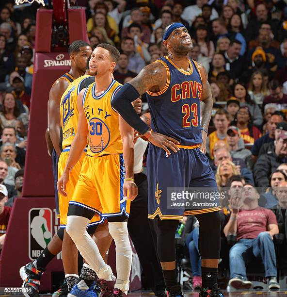 LeBron James of the Cleveland Cavaliers looks on against Stephen Curry of the Golden State Warriors on January 18 2016 at Quicken Loans Arena in...