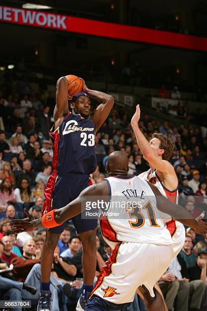 Lebron James of the Cleveland Cavaliers looks to pass over Adonal Foyle and Mike Dunleavy of the Golden State Warriors on January 20 2006 at the...