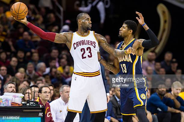 LeBron James of the Cleveland Cavaliers looks to pass while under pressure from Paul George of the Indiana Pacers during the first half at Quicken...