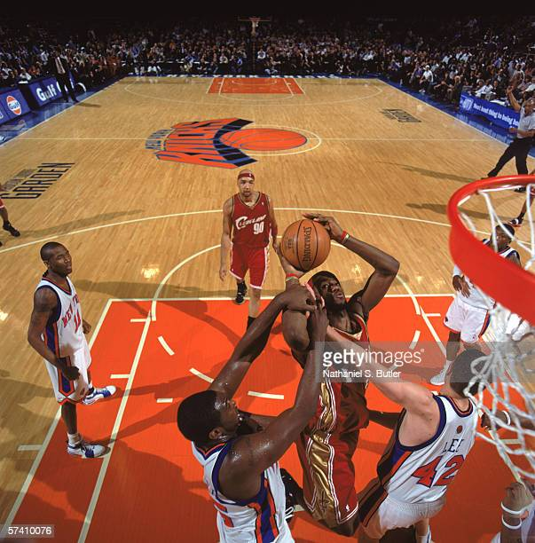 LeBron James of the Cleveland Cavaliers looks to put a shot up against Jackie Butler and David Lee of the New York Knicks at Madison Square Garden on...