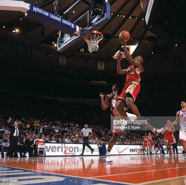 LeBron James of the Cleveland Cavaliers makes a layup Qyntel Woods against the New York Knicks at Madison Square Garden on April 5, 2006 in New York,...