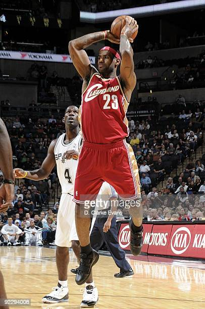 LeBron James of the Cleveland Cavaliers passes against Michael Finley of the San Antonio Spurs during a preseason game at ATT Center on October 16...