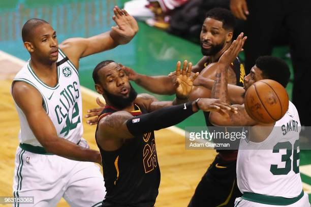LeBron James of the Cleveland Cavaliers passes the ball against Marcus Smart and Al Horford of the Boston Celtics in the first half during Game Seven...