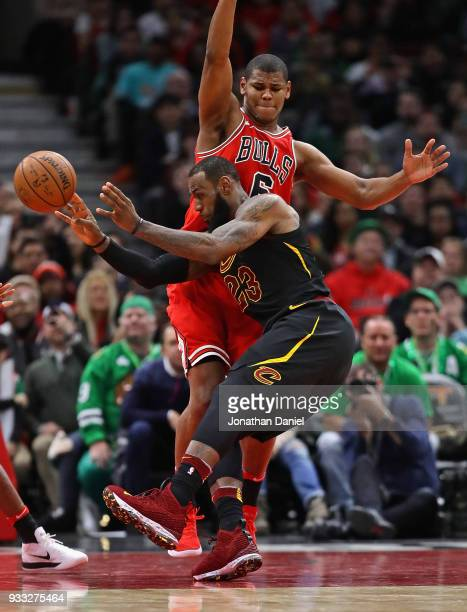 LeBron James of the Cleveland Cavaliers passes under pressure from Cristiano Felicio of the Chicago Bulls at the United Center on March 17 2018 in...
