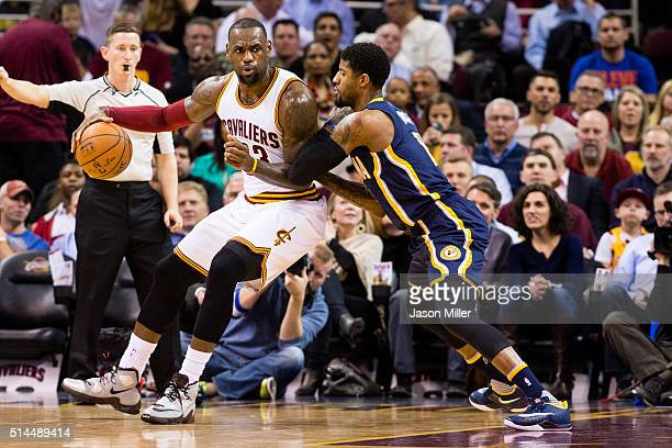 LeBron James of the Cleveland Cavaliers posts up against Paul George of the Indiana Pacers during the first half at Quicken Loans Arena on February...