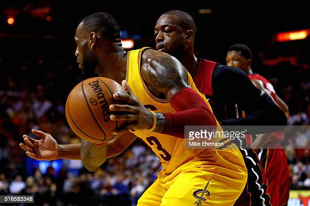 LeBron James of the Cleveland Cavaliers posts up Dwyane Wade of the Miami Heat during a game at American Airlines Arena on March 19 2016 in Miami...