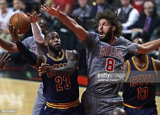 LeBron James of the Cleveland Cavaliers puts up a shot between Dwyane Wade and Robin Lopez of the Chicago Bulls at the United Center on December 2...