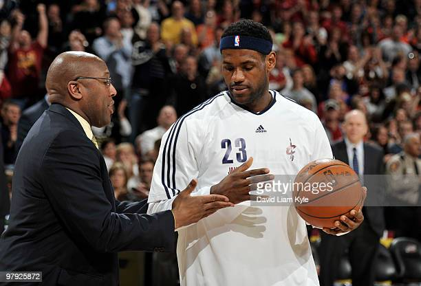 LeBron James of the Cleveland Cavaliers reaches out to shake head coach Mike Brown's hand after receiving the game ball from when LeBron became the...