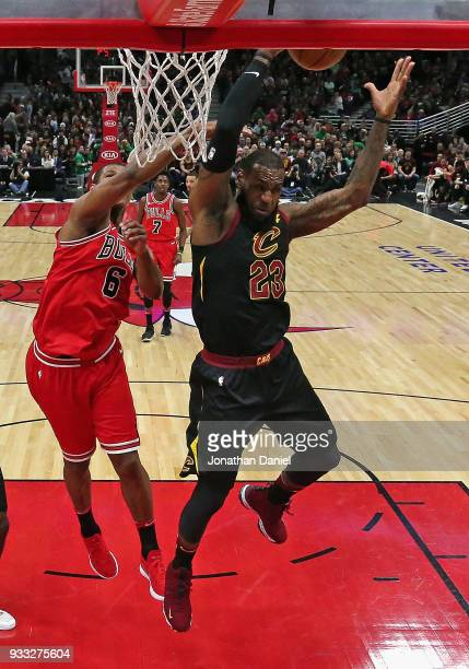 LeBron James of the Cleveland Cavaliers rebounds in front of Cristiano Felicio of the Chicago Bulls at the United Center on March 17 2018 in Chicago...