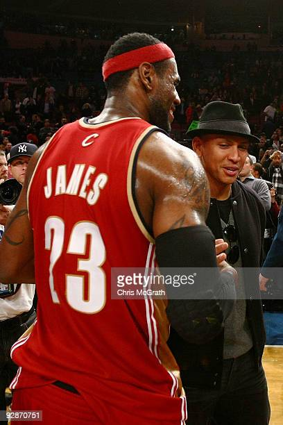 LeBron James of the Cleveland Cavaliers shakes hands with New York Yankees player Alex Rodriguez after defeating the New York Knicks at Madison...
