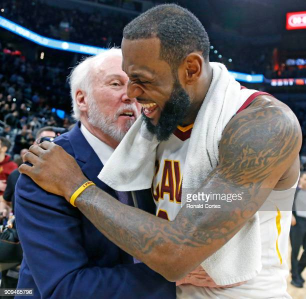 LeBron James of the Cleveland Cavaliers shares a laugh with head coach Gregg Popovich of the San Antonio Spurs at the end of the game at ATT Center...