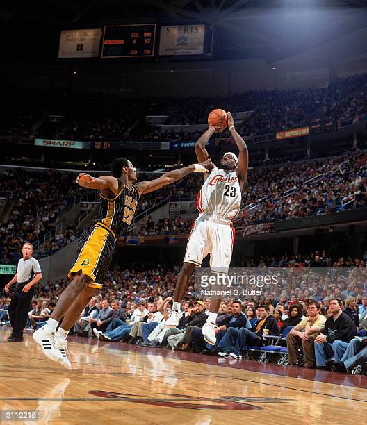 LeBron James of the Cleveland Cavaliers shoots a jumper over Ron Artest of the Indiana Pacers during the game at Gund Arena on March 14 2004 in...