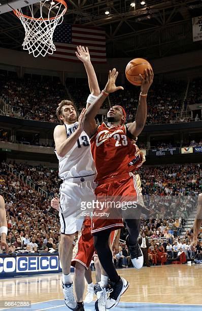 Lebron James of the Cleveland Cavaliers shoots a layup past Mehmet Okur of the Utah Jazz during a game between the Cleveland Cavaliers and Utah Jazz...