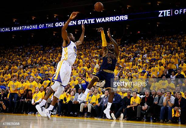 LeBron James of the Cleveland Cavaliers shoots against Andre Iguodala of the Golden State Warriors in the third quarter during Game One of the 2015...