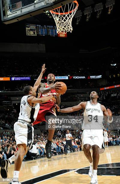 LeBron James of the Cleveland Cavaliers shoots between Malik Hairston and Antonio McDyess of the San Antonio Spurs on October 16 2009 at the ATT...