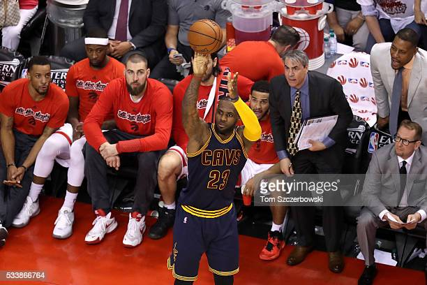 LeBron James of the Cleveland Cavaliers shoots in front of the Toronto Raptors bench in the third quarter in game four of the Eastern Conference...