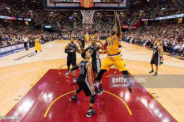 LeBron James of the Cleveland Cavaliers shoots over Kawhi Leonard and Danny Green of the San Antonio Spurs during the third quarter at Quicken Loans...