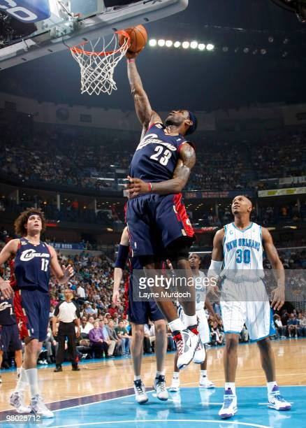 LeBron James of the Cleveland Cavaliers shoots over teammate Anderson Varejao as well as David West of the New Orleans Hornets on March 24 2010 at...